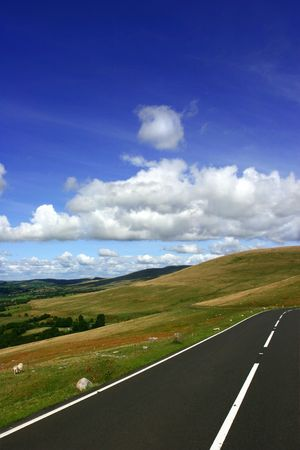 A rural mountain road in summer  with fields, trees and hills in the distance with a blue sky and  cumulus clouds. Set in the Brecon Beacons National Park, Wales, UK. Stock Photo - 309533