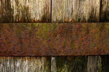 distill: Section of an old oak barrel, with a rusty band of metal holding the oak boards in place. Stock Photo
