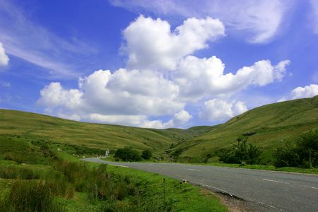 The Mountain Road, with hills on either side in the  Brecon Beacons National Park, Wales, United Kingdom set against a backdrop of blue sky and puffy white clouds. Stock Photo - 313036