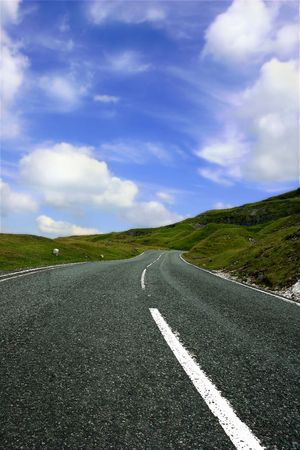 either: Steep, uphill  rural mountain road, with grass banks on either side and a blue sky with puggy white clouds.
