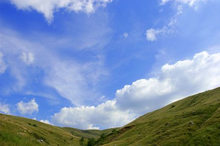 A valley in the Brecon Beacons National Park, Wales, UK with a blue sky and cumulus clouds.