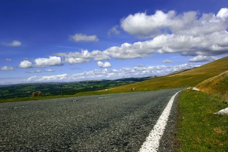skidding: Rural mountain road, with fields, trees and hills in the distance with a blue sky and puffy white clouds. Set in the Brecon Beacons National Park, Wales, UK. Stock Photo
