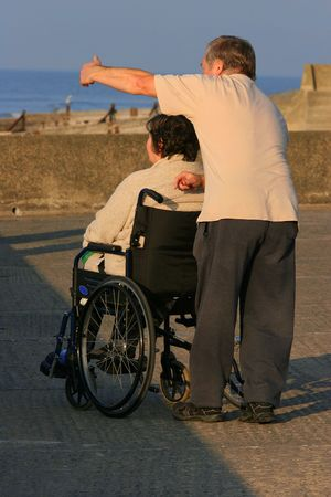 carers: A woman in a wheelchair with a man pointing something out to her in the distance. Stock Photo