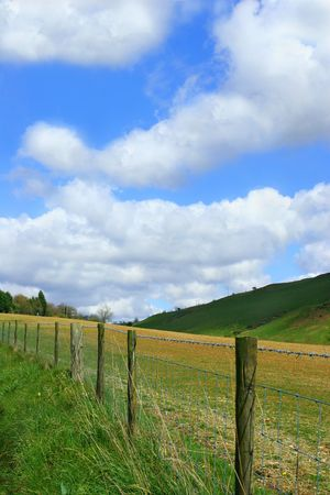 A wooden and wire fence in countryside with a blue sky and cumulus clouds. photo