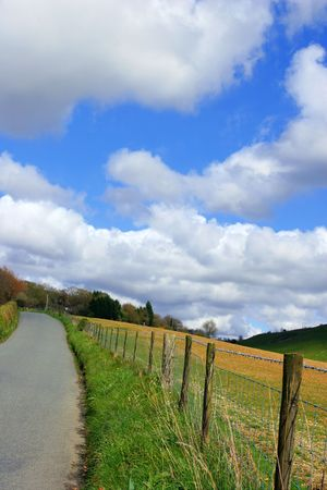 Narrow lane in the countryside with a wooden fence and fields to one side, on a blue sky day with puffy white clouds. photo