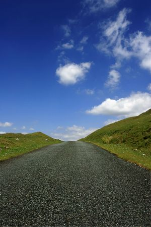 either: Up hill road in rural countryside with sloping verges on either side and a blue sky with puffy white clouds. Low perspective.