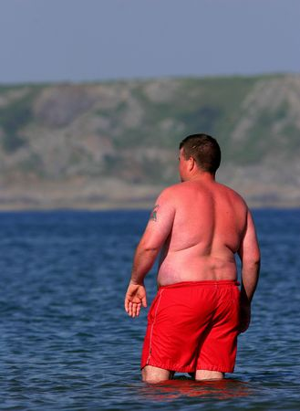 Over weight man wearing bright red swimming trunks, paddling in the sea and  heavily sunburnt.