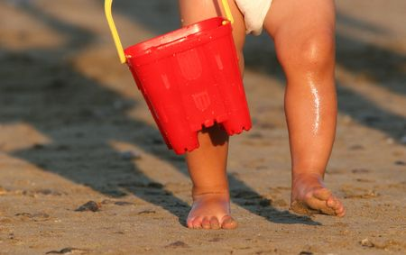 Legs and sandy feet of a toddler wearing a nappy and carrying a red plastic bucket and walking on a beach. Stock Photo