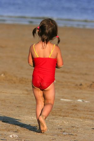 kiddies: Rear view of a  young child in a red and yellow bathing costume covered in sand, wandering towards the sea. Stock Photo