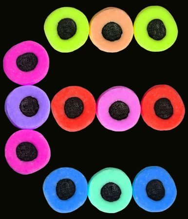 Twelve vividly colored licorice allsorts sweets on a black background.