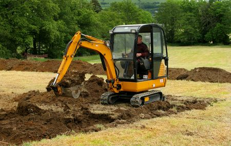 Man operating a mini digger in a field. Imagens