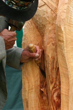carver: Wood carver with a chisel, carving a piece of wood. Stock Photo