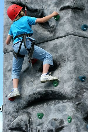 Young girl climbing  on a training rock face, wearing a harness and red hard hat. photo