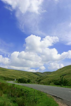 either: The Mountain Road, with hills on either side,  in the  Brecon Beacons National Park, Wales, United Kingdom set against a backdrop of blue sky and puffy white clouds.