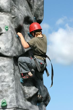 Boy climbing  on a training rock face, wearing a harness and red hard hat.