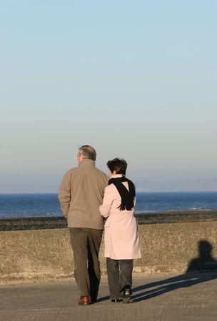 Elderly couple walikng together on a seaside promenade.