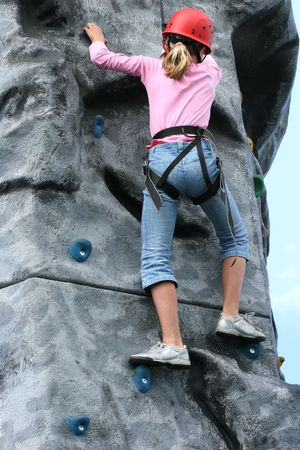 kiddies: Young girl climbing  on a training rock face, wearing a harness and red hard hat.