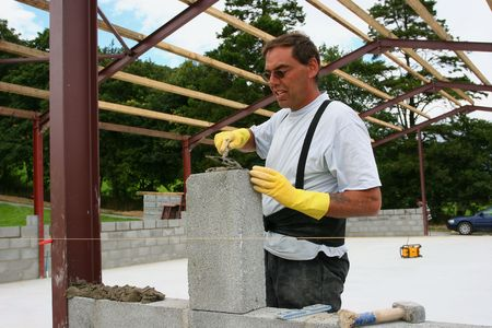 buildingsite: Man trowelling cement onto a concrete block on a building site and wearing rubber gloves to protect his hands.