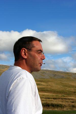 Sirva tener un cigarrillo y profundo en pensamiento, con colinas y un cielo azul con las nubes blancas puffy a la parte posterior. Foto de archivo - 326139