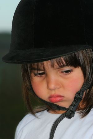 Face of a young child in a mood and pouting, wearing a riding hat. photo