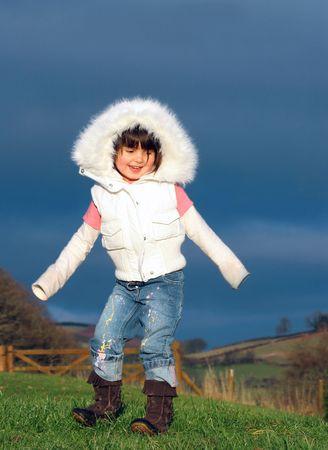 spattered: Peque�a muchacha que baila en la hierba en pantalones vaqueros salpicados pintura y una chaqueta blanca con una capilla de la piel.