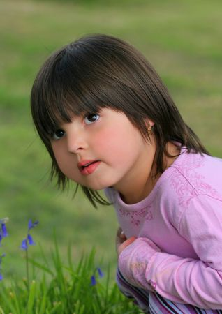 portraiture: Face and upper body of a little girl sitting on the grass next to some bluebells with a questioning look of on her face.