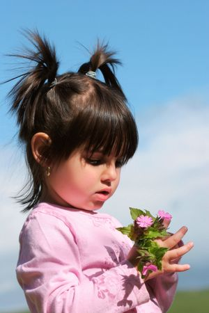 kiddies: Little girl with pigtails holding a handful of pink wild flowers.