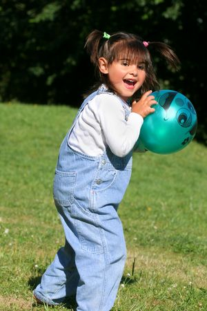 Little girl playing ball on the grass. photo