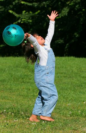 kiddies: Little girl in denim dungarees, with her arms outstretched, standing barefoot on the grass, trying to catch a large green plastic ball.