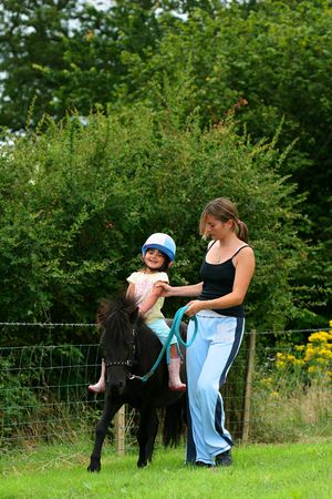 Little girl on a sheltland pony being taught how to ride by a female  instructor.