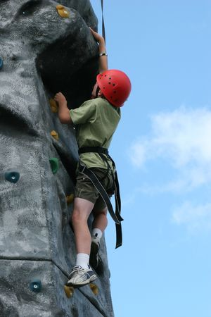 Boy climbing  on a training rock face, wearing a harness and red hard hat. photo