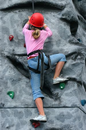 kiddies: Young girl wearing a safety harness and red hard hat, climbing on a training rock face. Stock Photo
