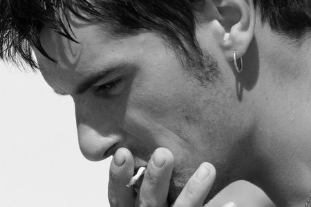 unhealthy thoughts: Profile of a man smoking a cigarette. In monochrome.