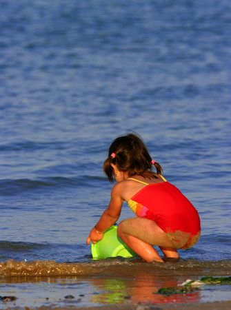 swimming costume: Little girl at the beach in a red swimming costume, trying to catch the waves in a bright lime green plastic bucket. Stock Photo