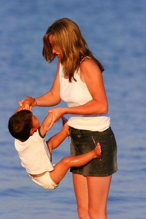 risky love: Madre su una spiaggia in estate con il suo figlio neonato in un pannolino, oscillante da lui le braccia.