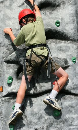 Boy climbing and stretching on a training rock face, wearing a harness and red hard hat.