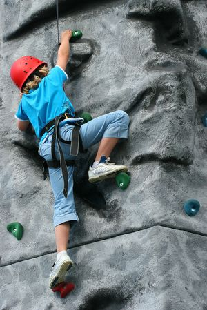 Young girl climbing  on a training rock face, wearing a harness and red hard hat.