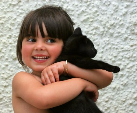 Little girl smiling and holding an all black kitten in her arms. Stock Photo