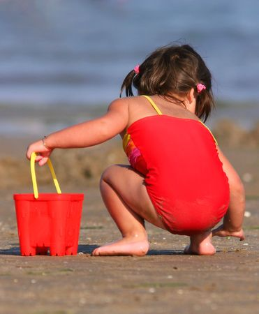 Little girl wearing a red swimming costume, holding a red bucket in her hand and gathering shells on the beach in summer. Rear view. Stock Photo