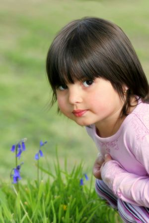 Face of a little girl sitting on the grass in spring next to some bluebells.