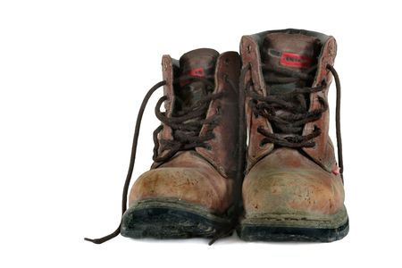 Dirty old brown leather steel toe capped workmans boots covered in mud, against a white background.