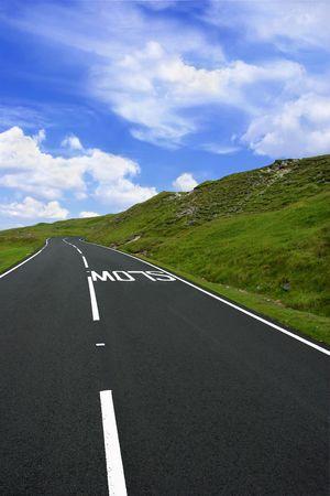 en mont�e: Uphill route de montagne en milieu rural avec un signe de ralentissement de marquage sur la route, avec des accotements de l'herbe sur chaque c�t� et un ciel bleu avec des nuages. Situ� dans le Parc national des Brecon Beacons, au Pays de Galles, Royaume-Uni.