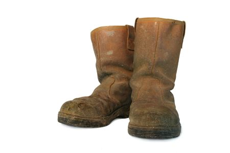 in twos: Pair of dirty brown leather builders boots against a white background.