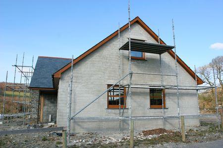 Vista lateral de una casa en construcción con los andamios erigidos para la parte frontal y lateral, sistema contra un cielo azul.  Foto de archivo - 367295