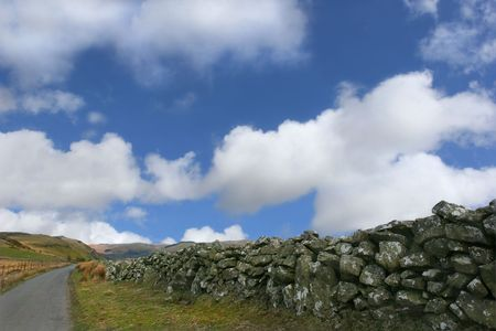 Old drovers road in the Cambrian Mountains, Wales, United Kingdom, with a dry stone wall to the right and hills in the distance, set against a blue sky with clouds. Stock Photo - 380369