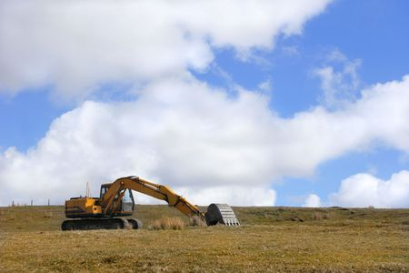 standing alone: Excavator digger standing alone and idle in a field, set against a blue sky with clouds.