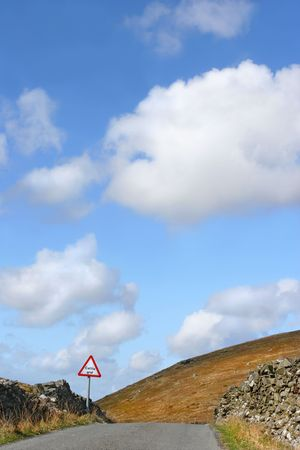 cattle grid: Old drovers road in the Cambrian Mountains Wales, United Kingdom, with stone walls and a cattle grid sign, set against a blue sky and cumulus clouds.