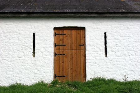 slits: Brown wooden barn door on an old white lime washed barn with air ventilation slits either side.