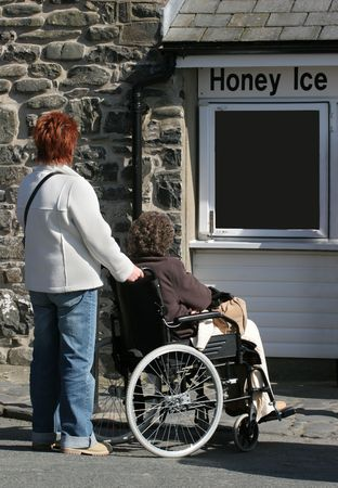 pushed: Elderly female in a wheelchair being pushed by a female carer. Stock Photo