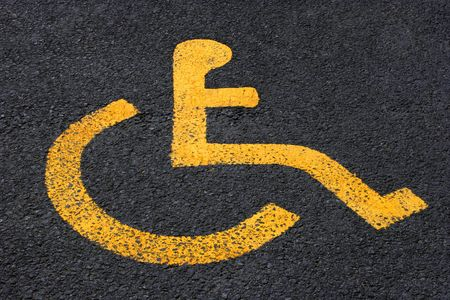 perk: Yellow disabled symbol in a car parking bay.